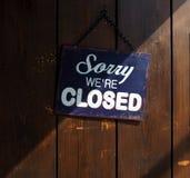 抱歉我们关于闭合,蓝色和白色标志的`在老木门,与划分它成一个清楚和黑暗的部分的阴影 免版税库存图片
