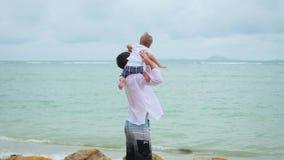 抱海滨的一个年轻人一个孩子 愉快的系列 股票视频