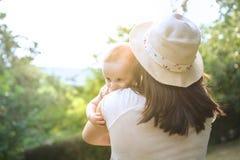 抱着一个婴孩本质上的年轻母亲 库存图片