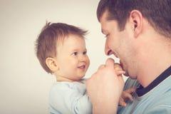 抱着一个微笑的婴孩的愉快的年轻人 r 免版税库存照片