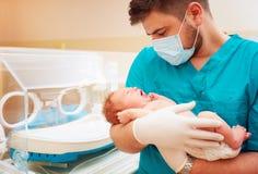 抱着一个新出生的婴孩的年轻成人人在医院 库存图片