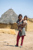 抱着一个婴孩的未认出的部族女孩在传统村庄 免版税库存图片