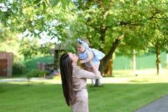 抱着一点女性婴孩的年轻愉快的母亲在庭院里 免版税库存照片