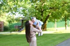 抱着一点女性婴孩的年轻母亲在庭院里 免版税库存照片