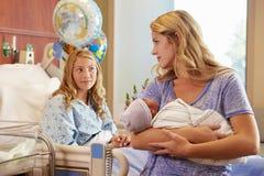抱着十几岁的女儿的新出生的婴孩的母亲在医院 库存照片
