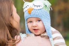 抱着可爱的矮小的婴孩的母亲室外 免版税图库摄影