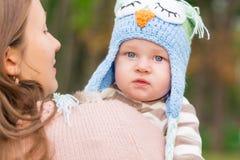 抱着可爱的矮小的婴孩的母亲室外 库存图片