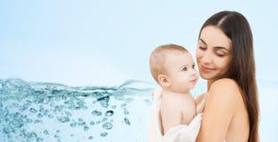 抱着可爱的婴孩的愉快的母亲 免版税库存图片