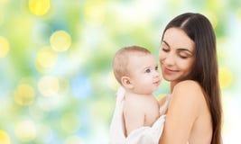 抱着可爱的婴孩的愉快的母亲 库存图片