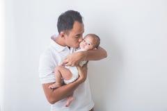 抱着和亲吻可爱的婴孩的年轻亚裔父亲 免版税库存照片