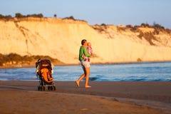 抱着和亲吻她的海滩的富感情的母亲婴孩 免版税图库摄影