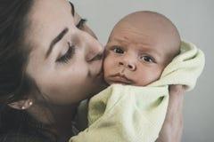 抱着和亲吻她的婴孩的母亲画象 库存照片
