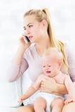 抱着哭泣的婴孩的妇女 免版税库存图片
