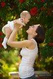 抱着在胳膊一个婴孩的愉快的妇女在庭院里 愉快的系列 库存图片