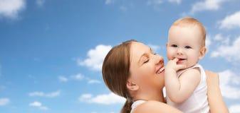 抱着在蓝天的愉快的母亲可爱的婴孩 免版税库存图片