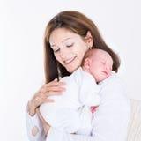 抱着她新出生的睡觉的婴孩的年轻母亲 免版税图库摄影