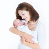 抱着她新出生的婴孩的美丽的年轻母亲 免版税库存照片