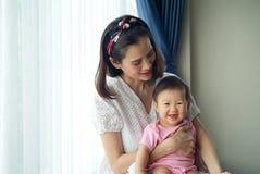 抱着她的她的胳膊的亚裔美丽的母亲可爱宝贝在家坐在窗口附近 免版税图库摄影