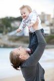 抱着她的她的胳膊的年轻母亲婴孩 库存图片