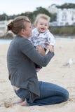 抱着她的她的胳膊的年轻母亲婴孩 库存照片