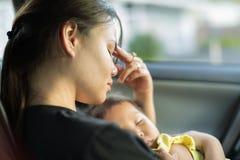 抱着她的婴孩的疲乏的被注重的母亲 免版税库存照片