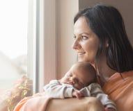 抱着她的胳膊的俏丽的妇女一个新出生的婴孩 免版税库存图片