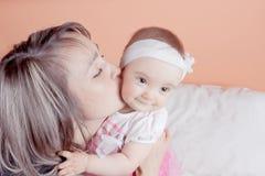 抱着她的婴孩的一个年轻母亲亲吻他。 免版税库存图片