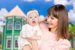 抱着她的婴孩的愉快的母亲画象 库存照片