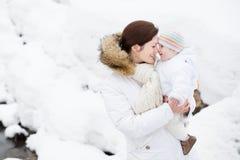 抱着她的婴孩的愉快的年轻母亲在多雪的公园 免版税库存照片