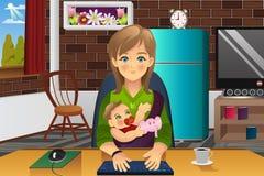 抱着她的婴孩的母亲,当在家时工作 库存图片