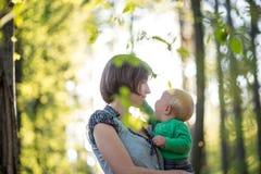 抱着她的婴孩的年轻母亲在森林地 库存照片