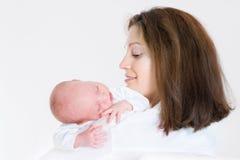 抱着她睡觉的新出生的婴孩的愉快的母亲 免版税库存图片