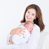 抱着她睡觉的新出生的婴孩的年轻母亲 库存图片