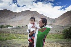 抱着她spiti谷的,印度的年轻和愉快的妇女逗人喜爱的婴孩 免版税图库摄影