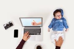 抱着婴孩的母亲,当研究膝上型计算机时 免版税库存照片