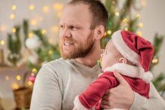 抱着小圣诞老人的父亲庆祝圣诞节 免版税库存照片