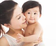 抱着微笑的儿童婴孩的愉快的母亲 免版税库存图片