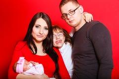 抱着新出生的婴孩的小孩女孩、父母 库存图片