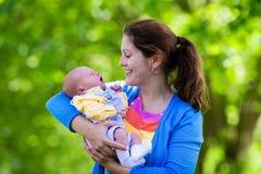 抱着新出生的婴孩的母亲在公园 免版税库存照片