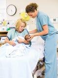 抱着的新出生的婴孩护士帮助的妇女在 图库摄影
