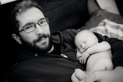 抱着睡觉的新出生的婴孩的父亲 免版税库存图片