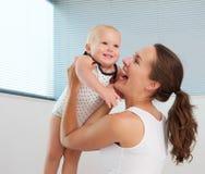 抱着逗人喜爱的微笑的婴孩的美丽的妇女 库存图片