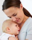 抱着逗人喜爱的婴孩的一名美丽的妇女的画象 免版税库存图片
