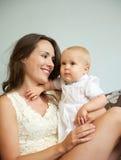 抱着逗人喜爱的婴孩的愉快的妇女户内 库存照片