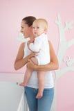 抱着逗人喜爱的婴孩的愉快的母亲在卧室 库存图片