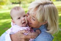 抱着逗人喜爱的婴孩的愉快的祖母 库存图片
