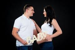 抱着题字婴孩的怀孕的夫妇 黑色背景 免版税库存图片