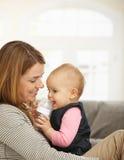 抱着婴孩的愉快的妈咪 免版税库存照片