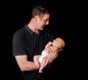 抱着婴孩的愉快的爸爸 免版税库存图片