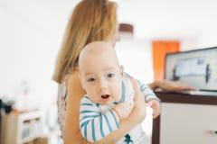 抱着婴孩的繁忙的母亲 库存照片